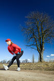 Woman stretches after cross country running Royalty Free Stock Images