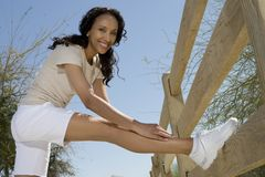 Woman Stretches Hamstring Against Fence Stock Images