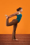 Woman Stretches Her Right Leg. Woman practising yoga stretches her leg backwards stock photography