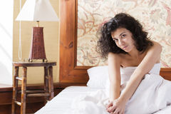 Woman stretches herself in bed after night Stock Photography