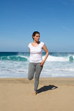 Woman stretches leg on beach Stock Images