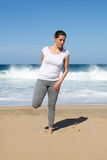 Woman stretches leg on beach Royalty Free Stock Image