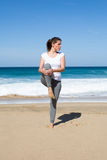 Woman stretches leg on beach Royalty Free Stock Photography