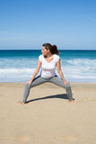 Woman stretches legs on beach Royalty Free Stock Images