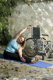 Woman Stretches Next to Wheelchair - Vertical Royalty Free Stock Image