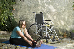 Woman Stretches Next to Wheelchair - Vertical. Woman stretches on blue yoga mat. Her legs are extended and her arms are reaching to her ankles. Vertically framed Stock Image