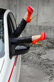 Woman stretches out her legs with shoes out the car window Stock Photos