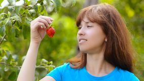Woman stretches out his hand with red strawberries on a green background stock video