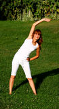 Woman stretching. Her midsection out in a green park Royalty Free Stock Photography
