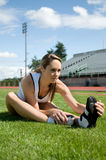 Woman Stretching. Young  woman stretching in the grass at a track. Vertically framed photo Royalty Free Stock Photo