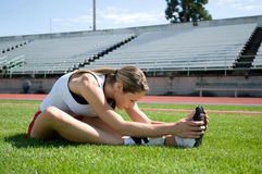 Woman Stretching. Young woman stretching on a lawn at a track with bleachers in the background. Horizontally framed photo Stock Photos