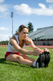 Woman Stretching. Young woman stretching in the grass at a track. Vertically framed photo Stock Photos