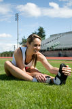 Woman Stretching. Young smiling woman stretching in the grass at a track. Vertically framed photo Stock Photography
