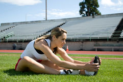 Woman Stretching. Young woman stretching on a lawn at a track with bleachers in the background. Horizontally framed photo Royalty Free Stock Photo