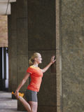 Woman Stretching Against Pillar In Portico Stock Photo