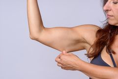 Woman stretching arm skin as she flexes muscle. Adult woman with brown hair stretching under arm skin as she flexes muscle over plain white background stock photos