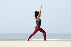 Woman stretching with arms raised. Portrait of a young woman stretching with arms raised at the beach Royalty Free Stock Photography