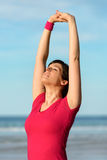 Fitness woman stretching on beach Stock Images