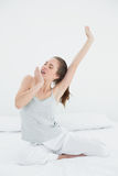 Woman stretching arms while yawning in bed Royalty Free Stock Images
