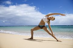 Woman stretching on beach. Stock Image