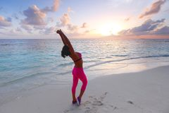 Woman stretching on beach Stock Image