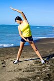 Woman stretching on the beach after running Stock Images