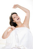 Woman stretching in bed. Young woman stretching while yawning in bed Royalty Free Stock Photos