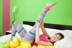 Woman stretching in bed Stock Photography