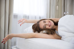 Woman stretching on the bed Royalty Free Stock Image