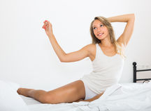 Woman stretching on bed stock photo