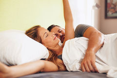 Woman stretching in bed with sleeping boyfriend Royalty Free Stock Photo