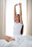 Woman stretching in bed after wake up, entering a day happy and relaxed after good night sleep. Sweet dreams, good Stock Photos