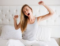 Woman stretching in bed after wake up, front view. Good morning stock image