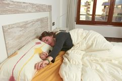 Woman stretching in bed after waking up. Woman stretching in bed after waking up wake happy lifestyle lazy pillow young bedroom rest relax person beautiful home stock photography