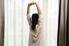 Woman stretching in bedroom after wake up, back view royalty free stock image