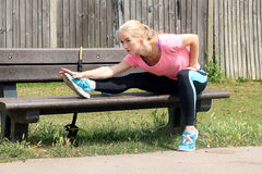 Woman stretching on bench Stock Photos