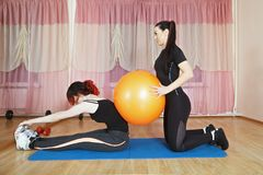 Stretching with the ball. Woman stretching body while coach helps her pressing the ball on her back. Horizontal shot Royalty Free Stock Photo