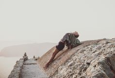 Woman stretching body on stones in Monolithos, Rhodes, Greece stock photography