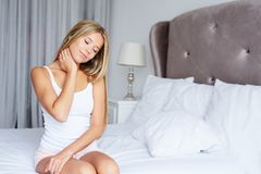 A woman is stretching a cervical spine. In her bed stock image