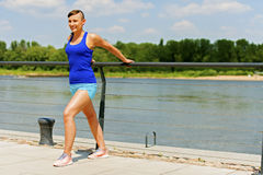 Woman stretching in city park by the river. Smiling. Stock Photo