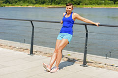 Woman stretching in city park by the river. Smiling. Royalty Free Stock Photography