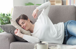 Woman stretching on the couch Stock Photo