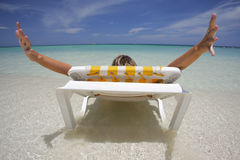 Woman Stretching in Deckchair. Nice vacation picture with woman sitting on a lounger in pretty tropical water Stock Images