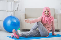 Woman stretching while doing exercise at home Royalty Free Stock Photo