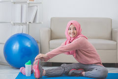 Woman stretching while doing exercise at home Stock Image