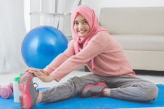 Woman stretching while doing exercise at home Stock Photo