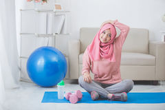 Woman stretching while doing exercise at home Royalty Free Stock Image