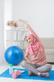 Woman stretching while doing exercise at home Royalty Free Stock Photos