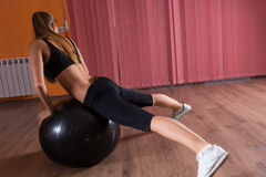 Woman Stretching with Exercise Ball in Studio Royalty Free Stock Image