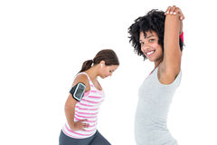 Woman stretching while female friend exercising Royalty Free Stock Photos